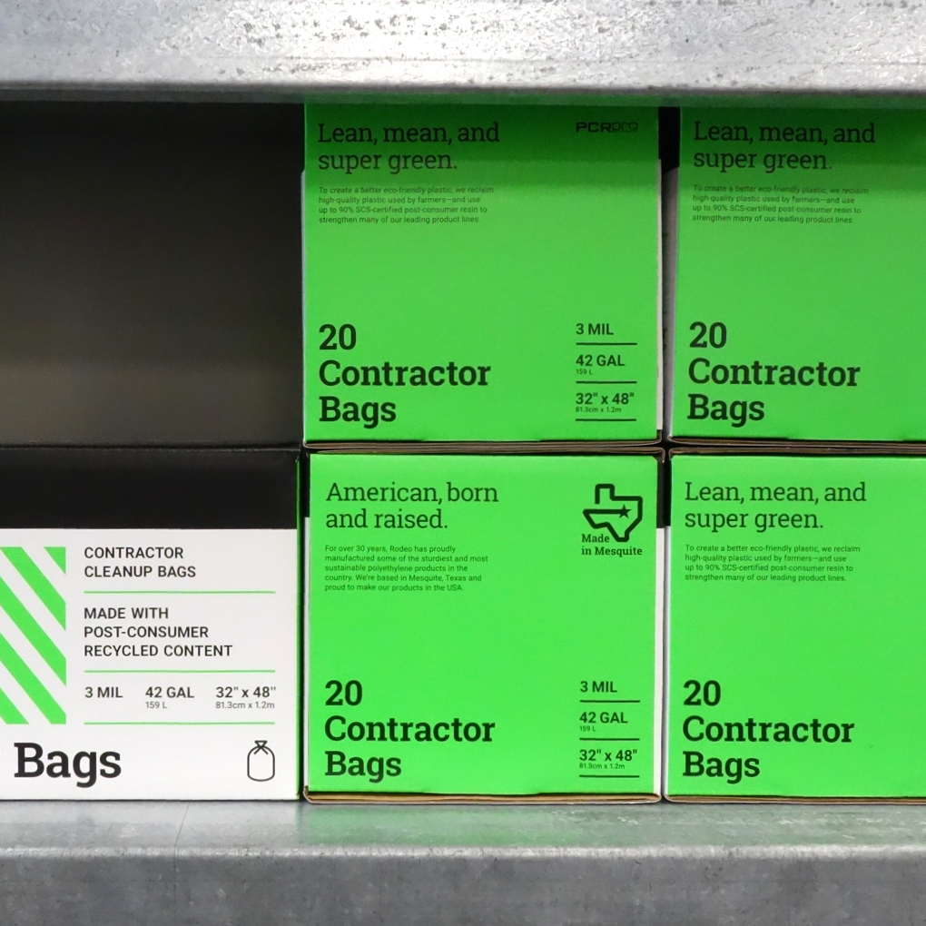 """A stack of Rodeo Plastics 20 contractor bag packages imprinted with the phrase """"American born and raised."""""""