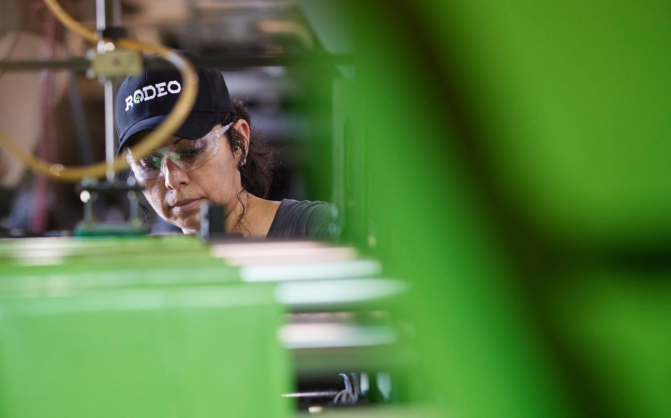 Rodeo Plastics worker in a company branded hat and saftety glasses works among the factory machinery.