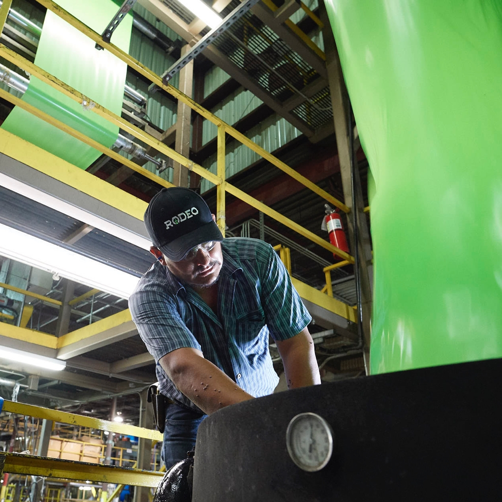 A worker in a company branded hat bends over to operate machinery in the Rodeo Plastics factory.