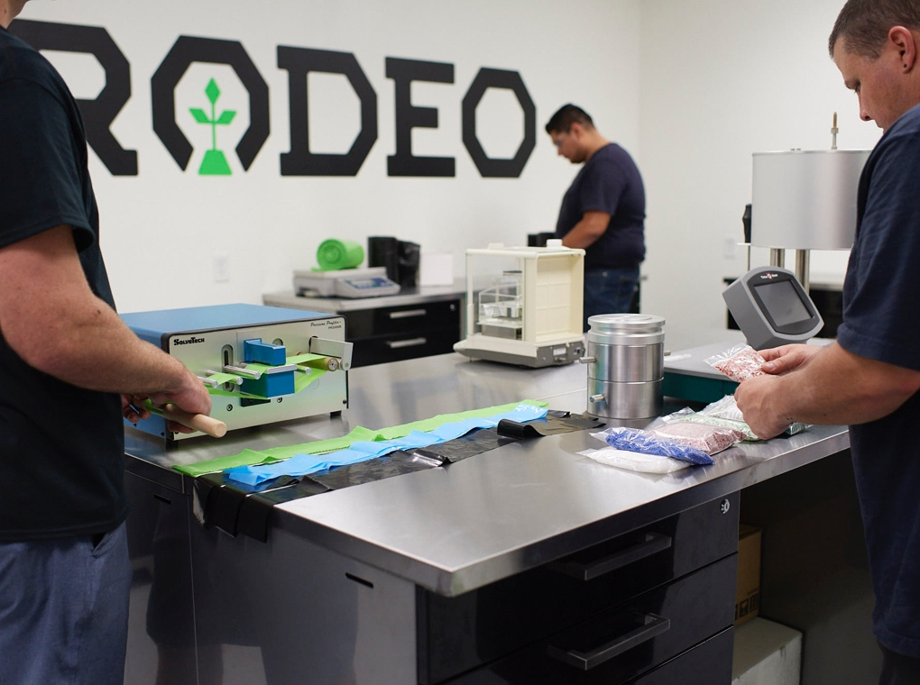 Three workers inspect products on tables in front of a wall painted with a large Rodeo Plastics logo.