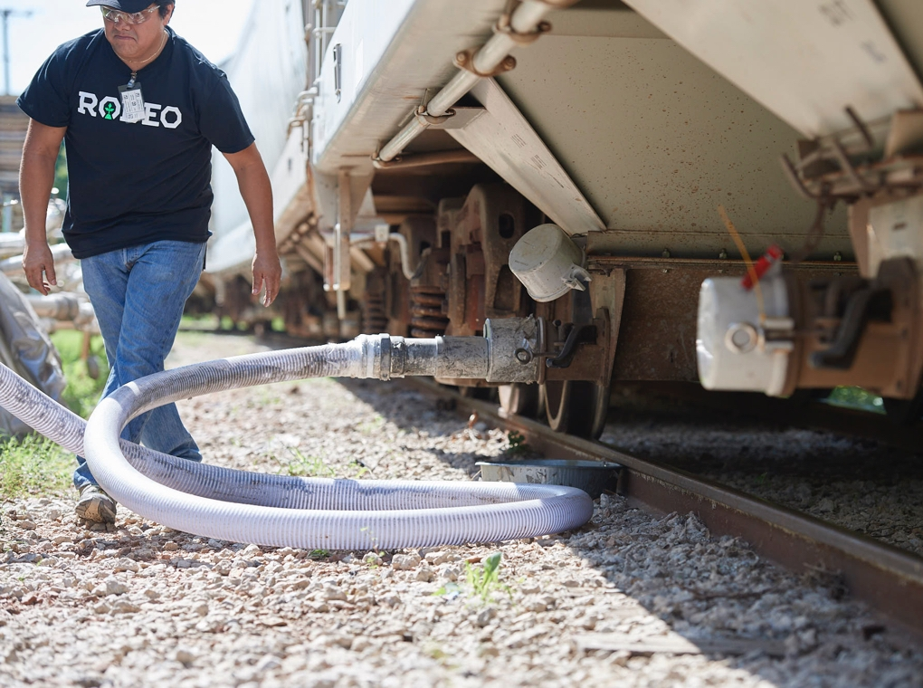 A worker in a Rodeo Plastics tee shirt attaching a hose to a railroad freight car tanker.