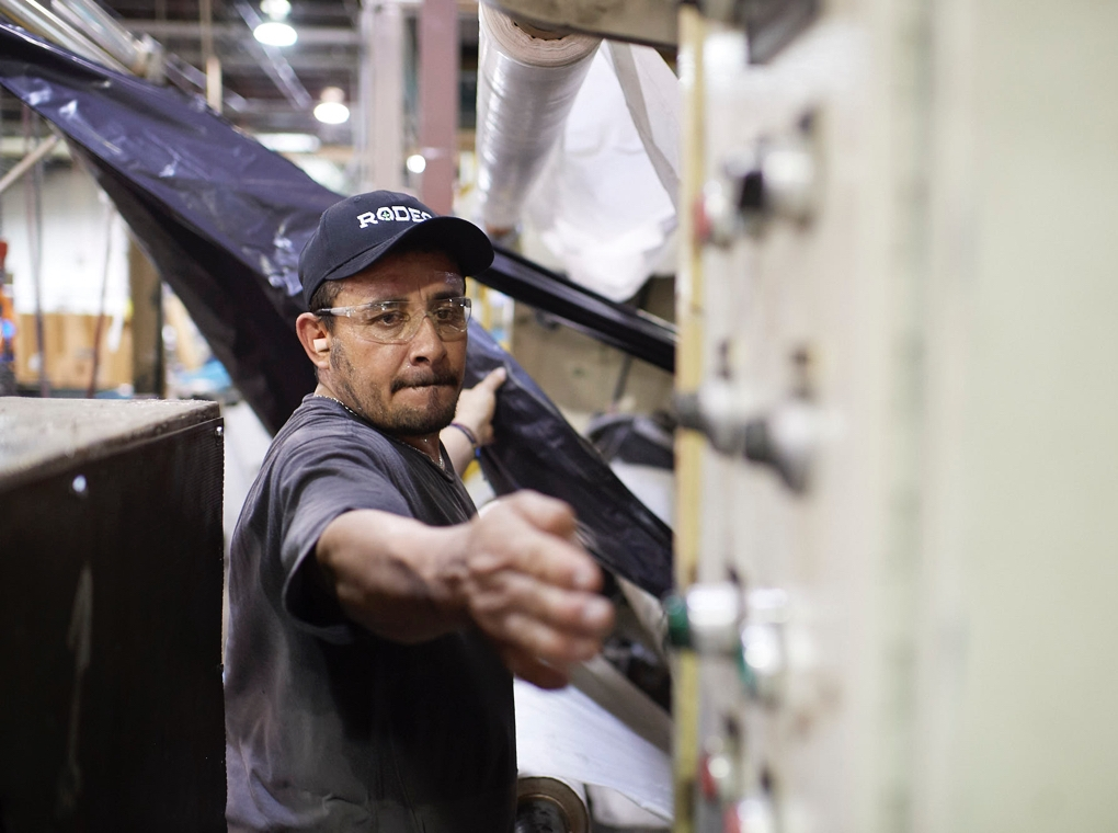 A worker in a Rodeo Plastics cap reaches out to flip a switch on machinery in the company's Mesquite Texas factory.