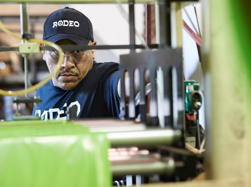 A worker in a Rodeo Plastics tee shirt and cap operates machinery in the company's Mesquite Texas factory.