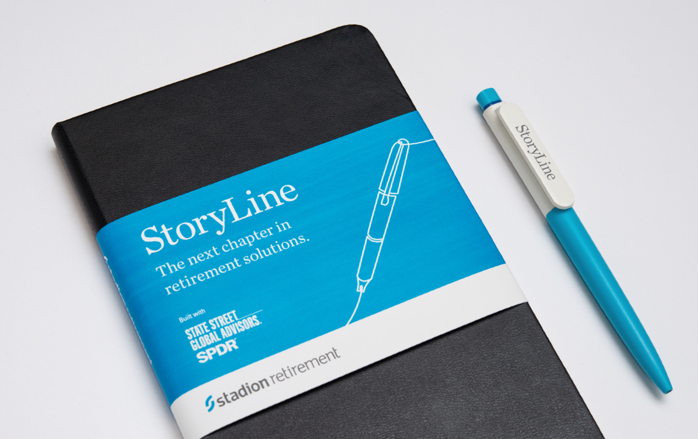 Notebook wrapped in Stadion StoryLine branding rests next to branded pen.