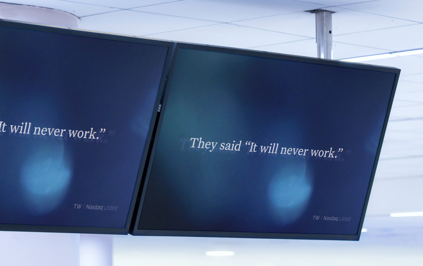 "Overhead TV screens displaying an abstract video still frame with the words ""They said it will never work."""