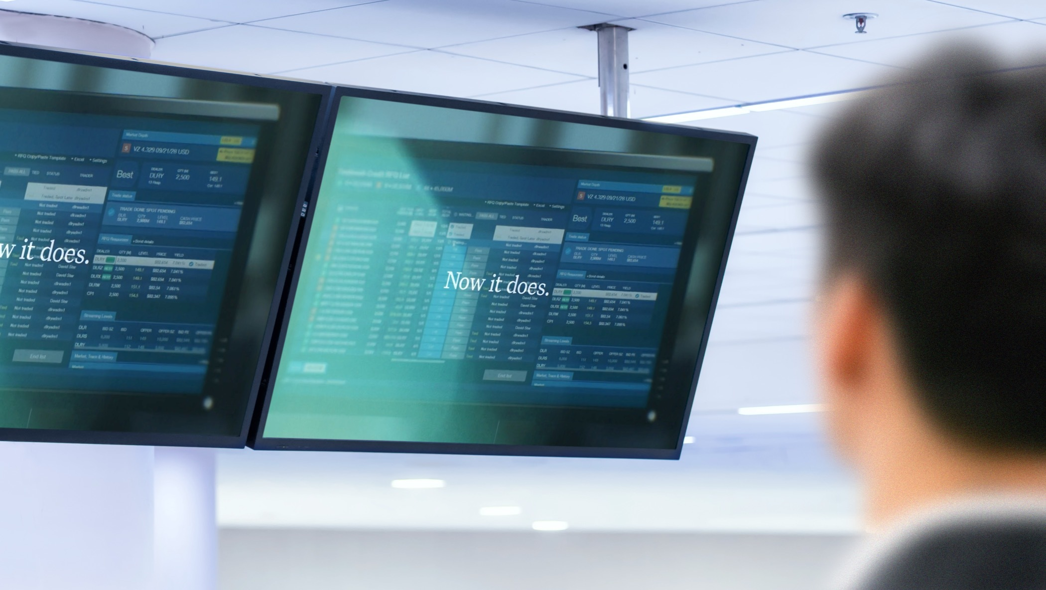 "Overhead TV screens displaying a video still frame with the words ""Now it does,"" with a blurry figure in the foreground"