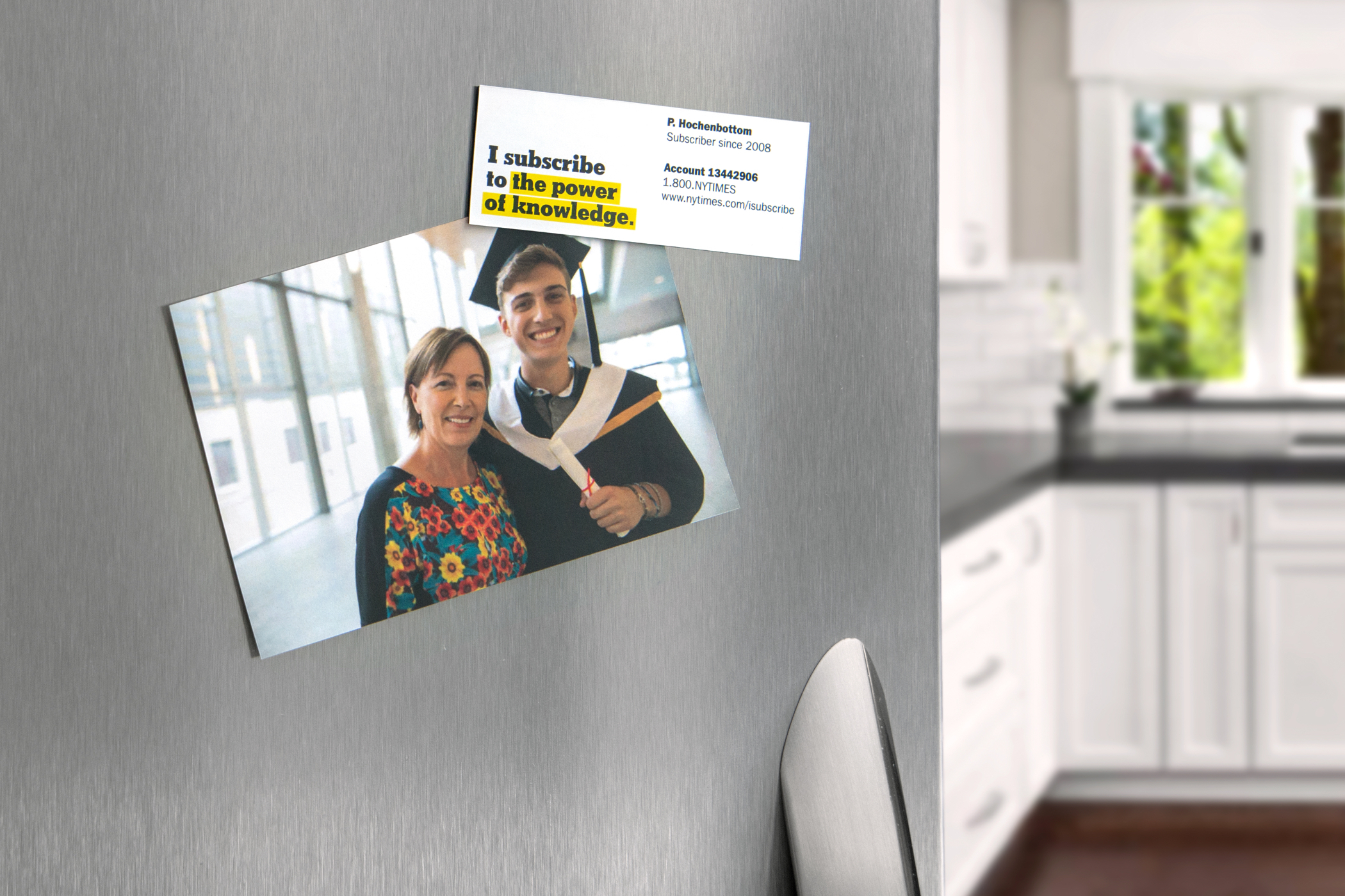 "A New York Times promotional magnet that reads ""I subscribe to the power of knowldege"" holding a photo of graduate and his mom to a refrigerator."