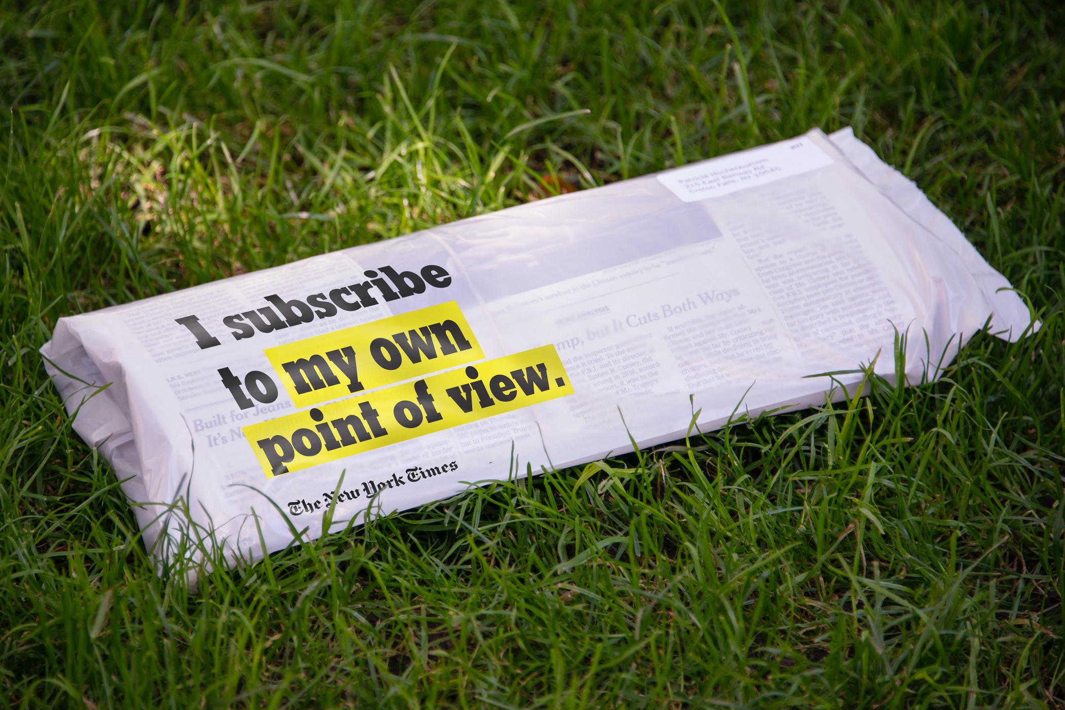 "A New York TImes paper in plastic delivery bag printed with the text ""I subscribe to my own point of view"" on a grassy lawn."