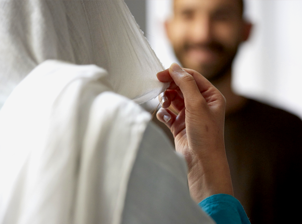 An example of Think Responsive brand photography: hand pulls at a transparent white cloth head scarf with a figure in the background.