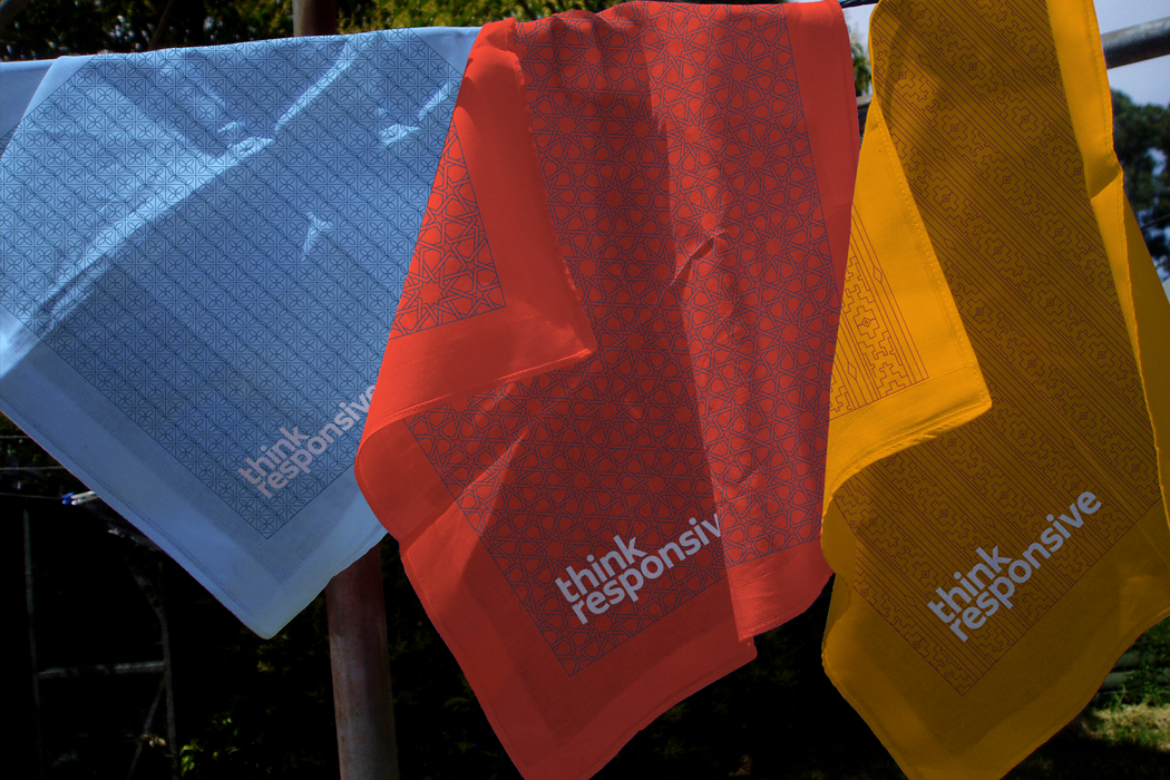 Three Think Responsive branded scarves in blue red and orange printed with the intricate brand line patterns.