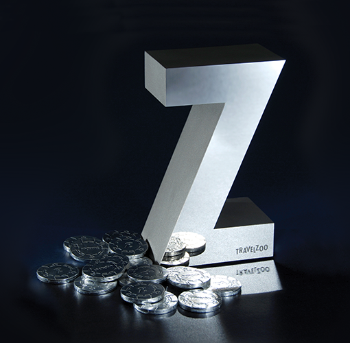A large, silver letter Z shaped trophy with the Travelzoo logo and a stack of award medallions.