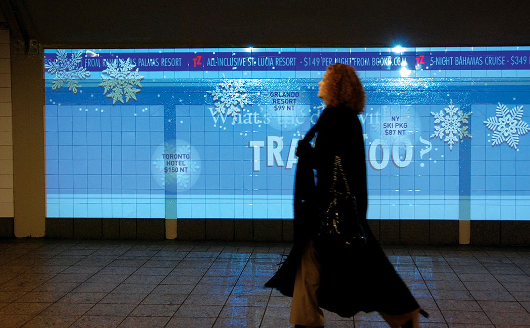 A figure walks in front of a large Travelzoo digital ad projected on a tile wall at Grand Central Station in New York City.