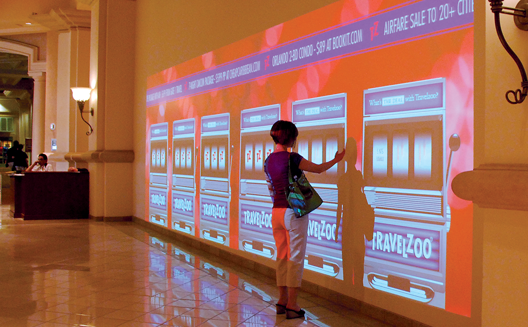 A person plays an oversized, Travelzoo-branded interactive virtual slot machine at the Travelzoo awards in Las Vegas.