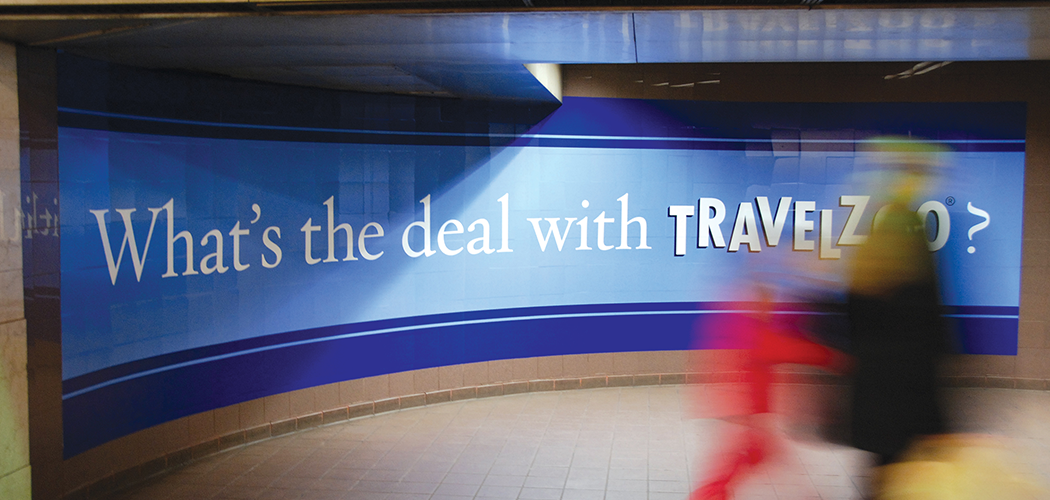 """A mural-sized advertisement on a curved tile New York CIty subway wall that reads """"What's the deal with Travelzoo?"""""""