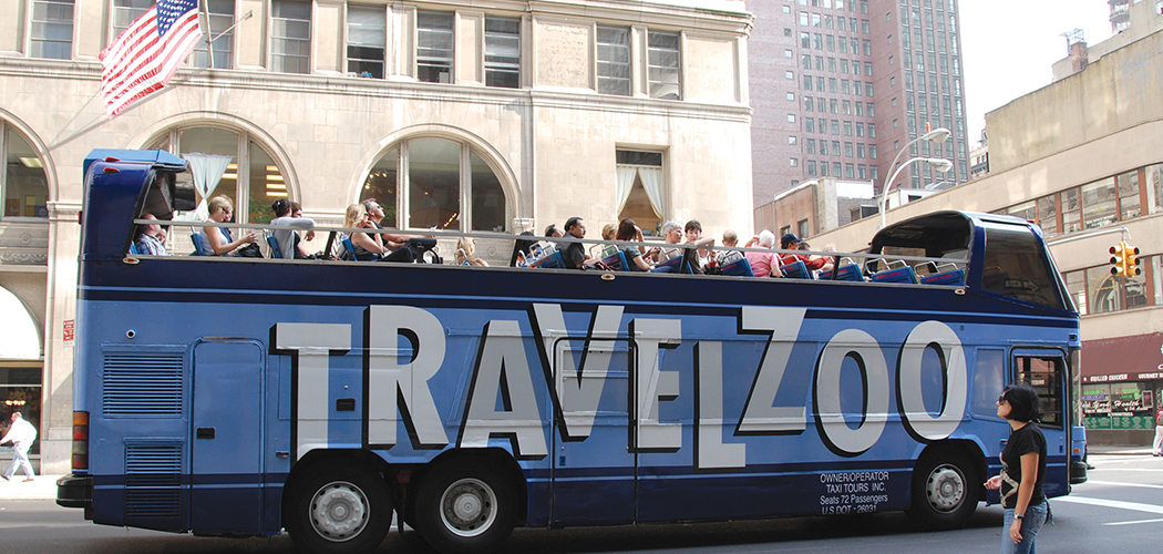 An open-top tourist bus on a city street with a giant Travelzoo logo painted on the side.