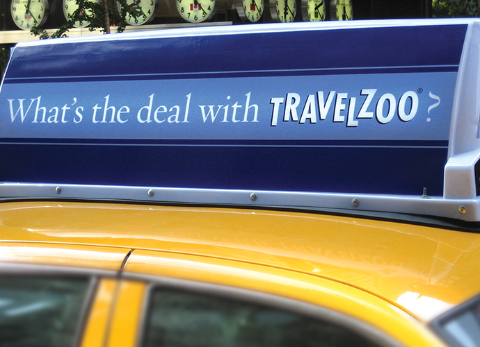 """Close up of a taxi-top sign with the text, """"What's the deal with Travelzoo?"""""""