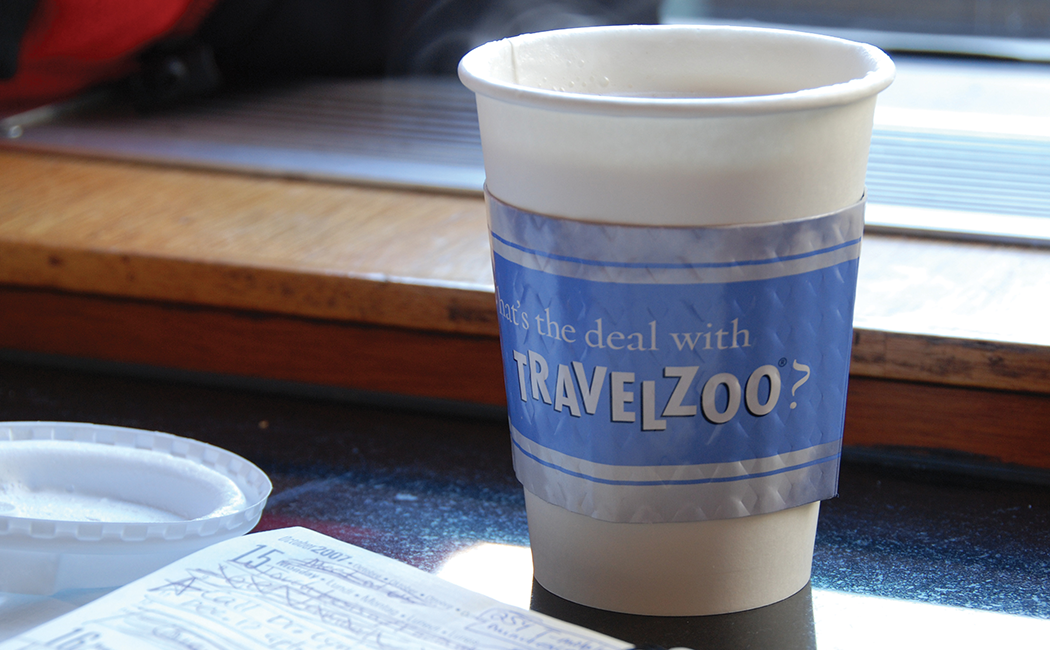 """Close up of a to-go coffee cup with a cozy printed with the text """"What's the deal with Travelzoo?"""""""