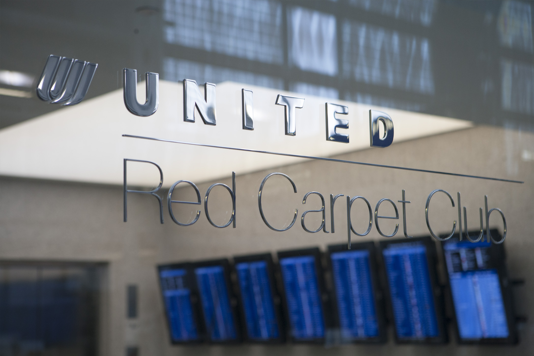 United Airlines Red Carpet Club signage in a glass partition.