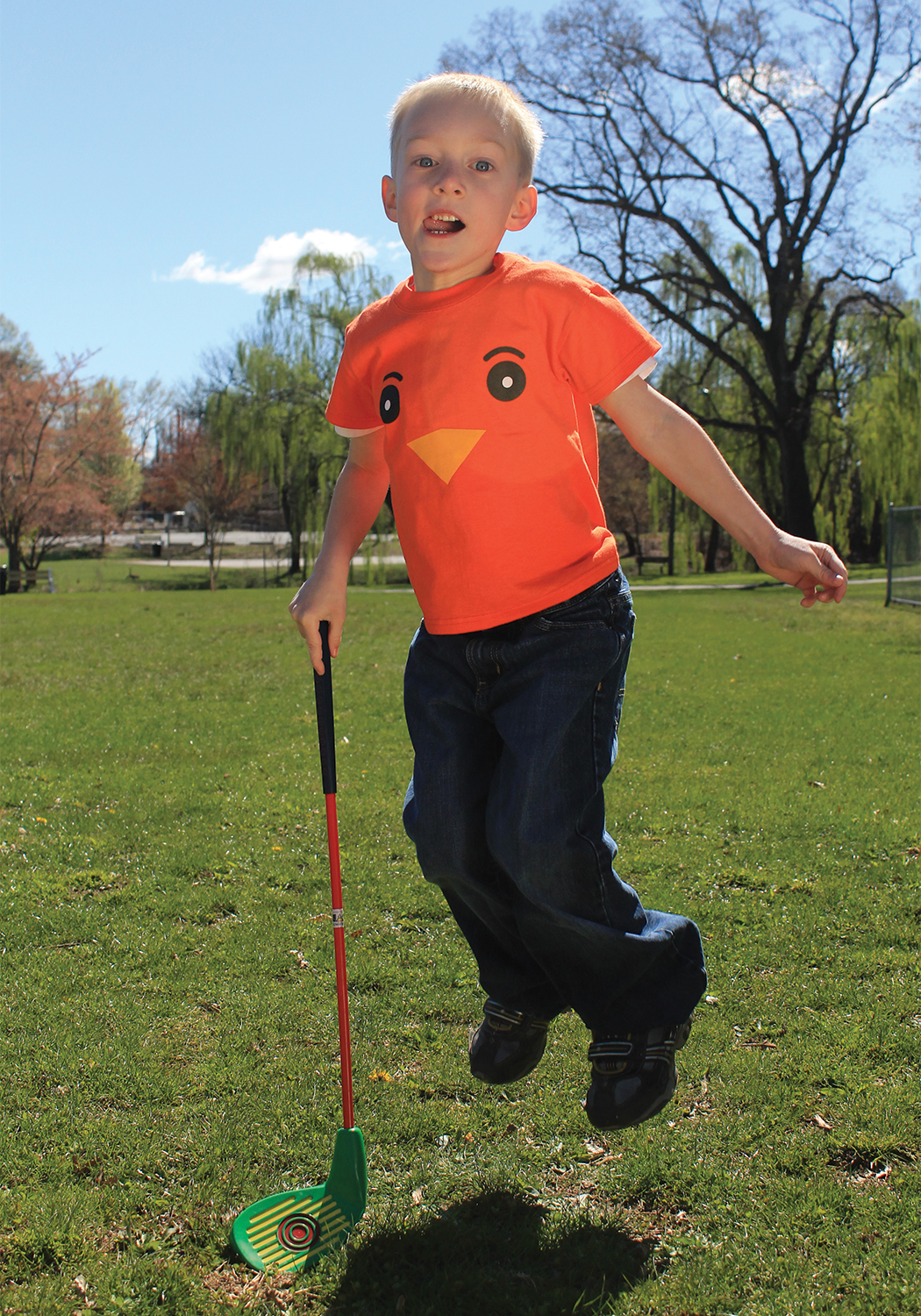 """A young boy with a plastic golf club leaping up in his Urban Golf Academy """"birdie"""" mascot T shirt."""