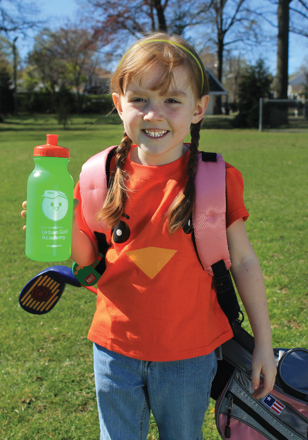 """A young girl carrying a golf bag with an Urban Golf Academy water bottle and """"birdie"""" mascot T shirt."""