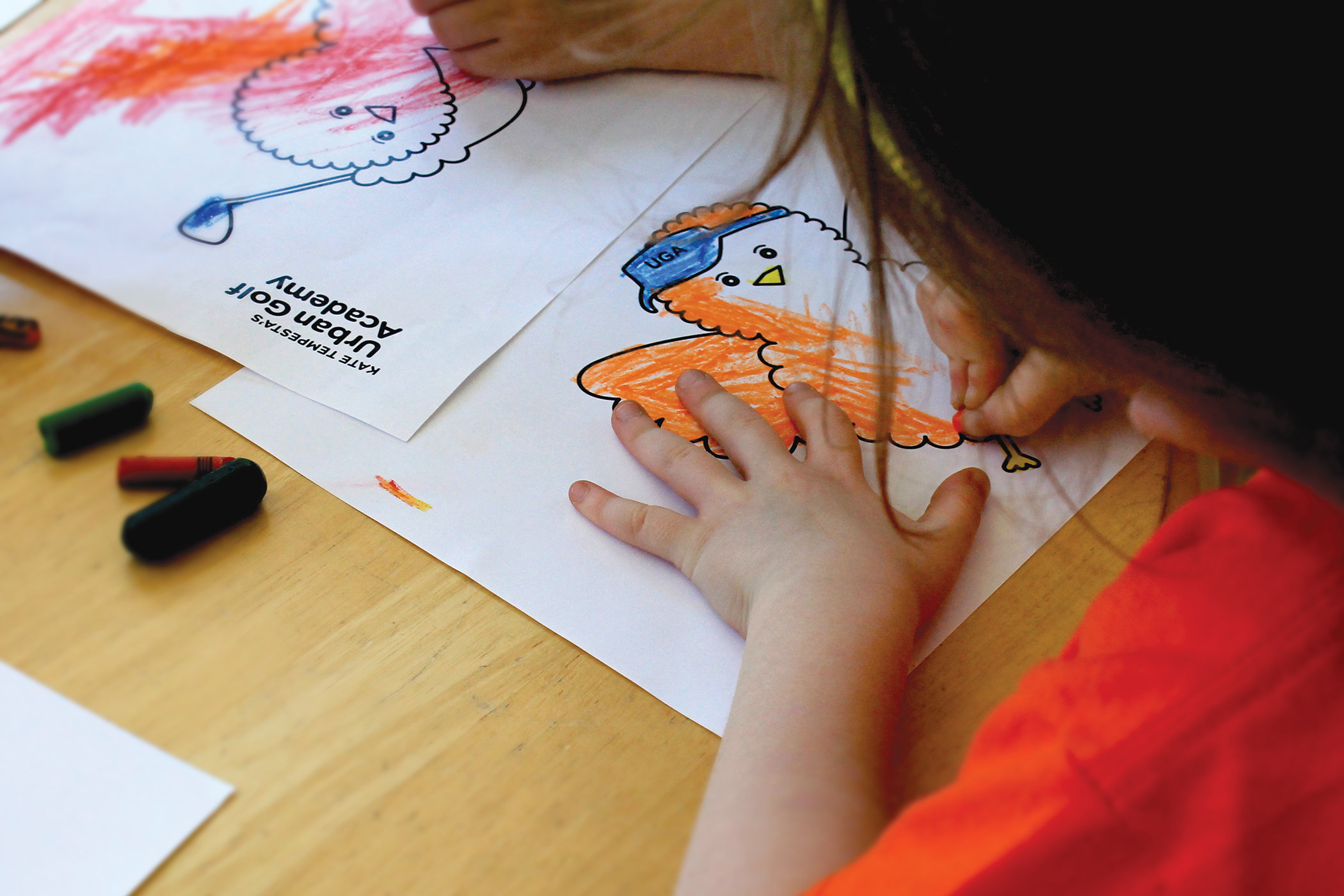 Close up of a student filling in a coloring book page of Birdie, the illustrated orange Urban Golf Academy mascot.