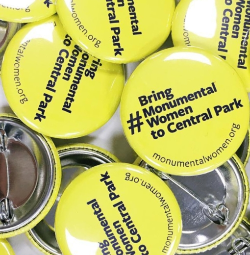 "Bright yellow circular pins that say ""Bring monumental women to central park"" and the website monumentalwomen.org"