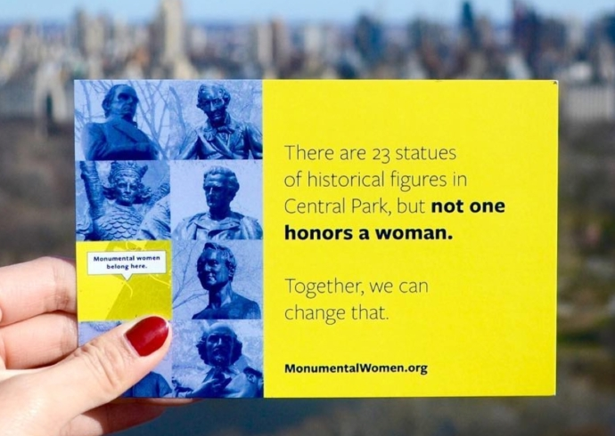 "hand holding a postcard that says ""There are 23 statues of historical figures in Central Park, but not one honors a woman. Together, we can change that. Monumentalwomen.org"""