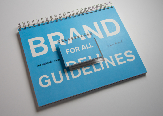 A large blue bound brand book with an identical tiny book perched on top of it with the title text, Brand for all guidelines.