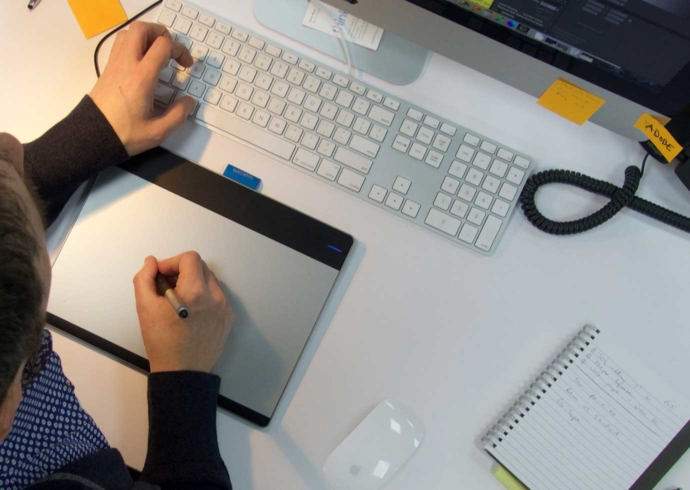 A view from above of a Thinsko designer at at desk using a stylus and drawing tablet.