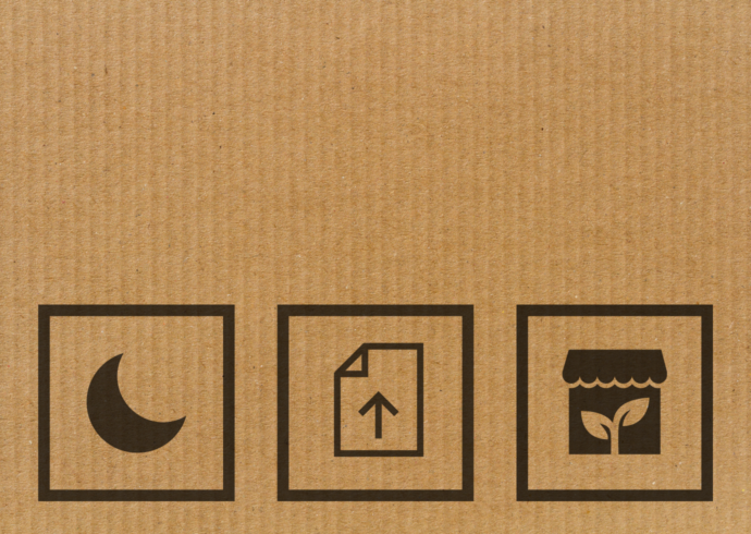 Cardboard background with symbols for dark mode, uploading paper document digitally, and eco-friendly businesses.