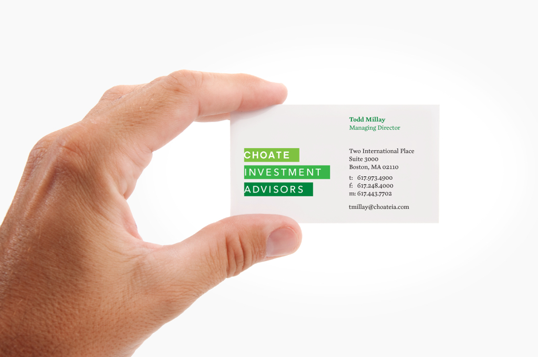 Close up of a hand holding a Choate Investment Advisors business card, with its white type on stacked green bars logo.