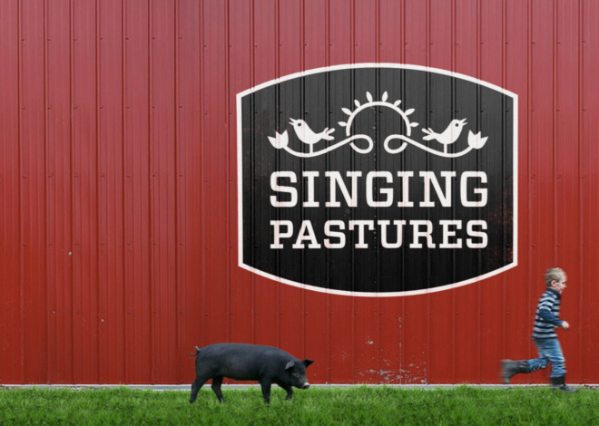 A large Singing Pastures logotype painted on a red barn wall with an illustration of a bird perched on a flowered vine.
